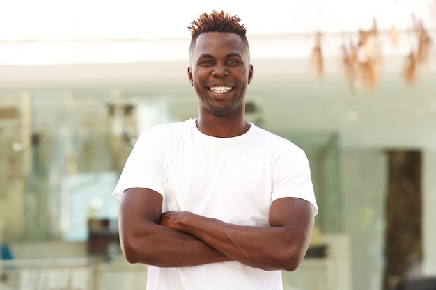 Smiling african american man with arms crossed standing outside