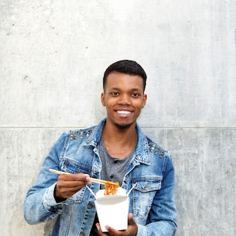 Smiling african american man with noodles in fast food box