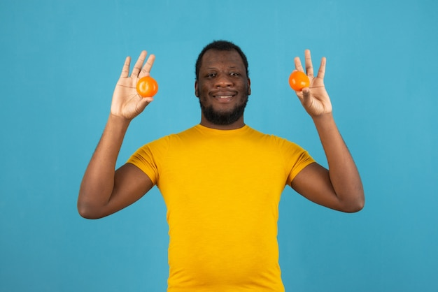 Smiling african american man with a tangerine in both hands , stands over blue wall.