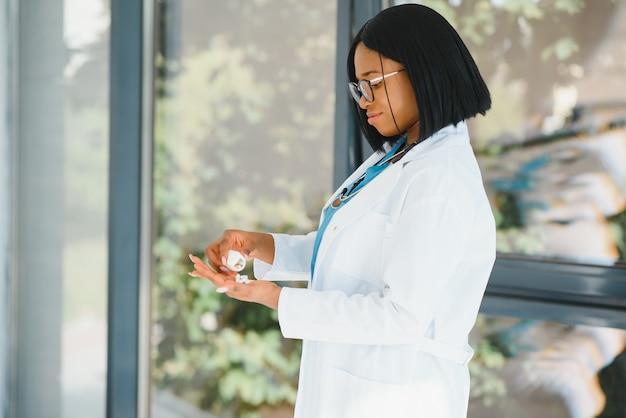 Улыбаясь афро-американская медсестра со стетоскопом, держащая таблетку