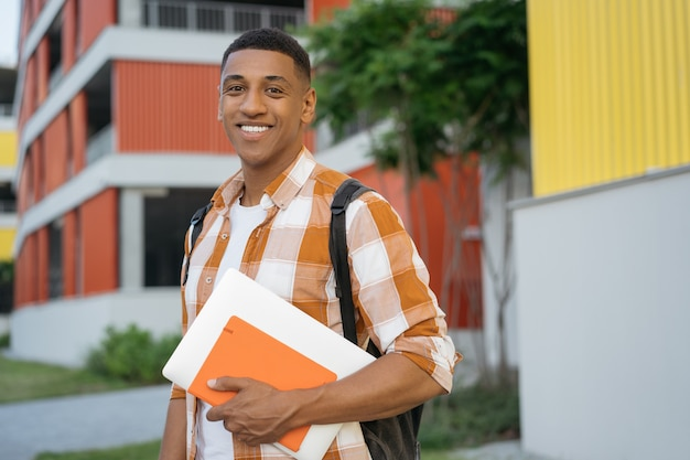 Улыбающийся афро-американский студент, смотрящий в камеру в университетском городке концепция образования