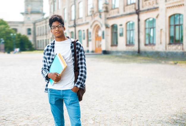 Smiling african american student with glasses and with books near college. portrait of a happy black young man standing on a university.