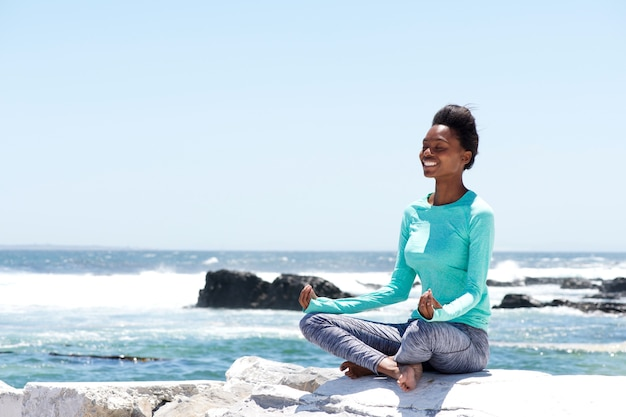 Smiling african american woman doing yoga by the sea