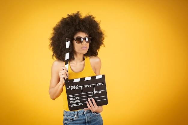 밝은 노란색 배경에 고립 된 포즈 캐주얼 바지에 아프리카 계 미국인 여자를 웃 고.