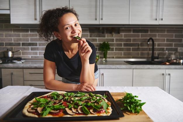 熱いピザとバジルを味わい、笑顔、家庭の台所の背景の上にカメラでポーズをとって台所のテーブルに寄りかかって笑顔のアフリカ系アメリカ人の女性