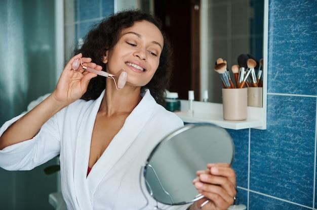 웃고 있는 아프리카계 미국인 여성이 옥 롤러 마사지기로 얼굴을 마사지하고 작은 원형 화장 거울에 비친 자신의 모습을 바라보고 있습니다.