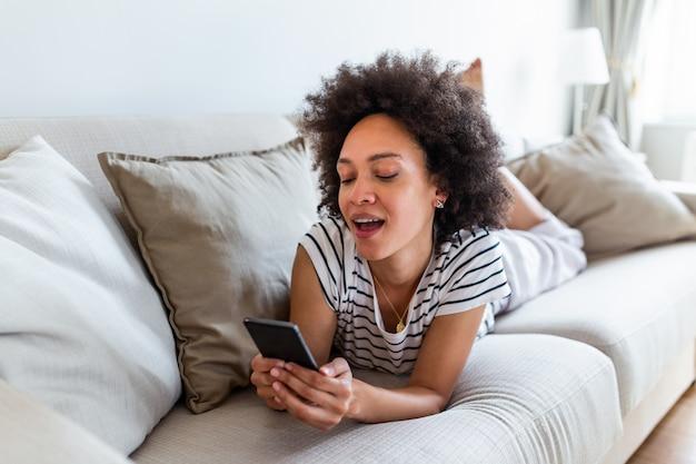 自宅のソファーに座っている間彼女の携帯電話でメッセージを読んで笑顔のアフリカ系アメリカ人女性。