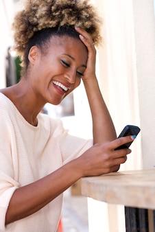 휴대 전화 야외에서 문자 메시지를 읽고 웃는 아프리카 계 미국인 여자