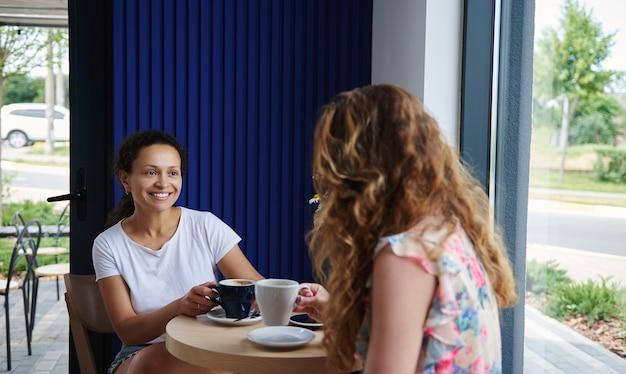 カフェのテーブルに座って、コーヒーを飲みながらヨーロッパ人の友人とおしゃべりしているアフリカ系アメリカ人の女性の笑顔。カフェで休んでいる女の子