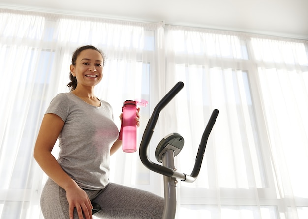 Smiling african american woman sitting on a spin bike and holding a bottle with water
