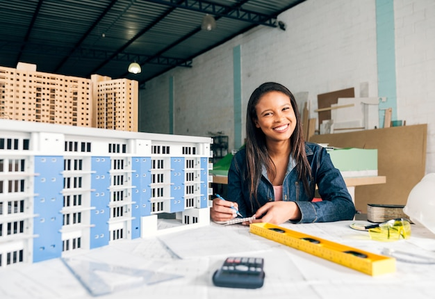 Smiling african-american woman taking notes near model of building