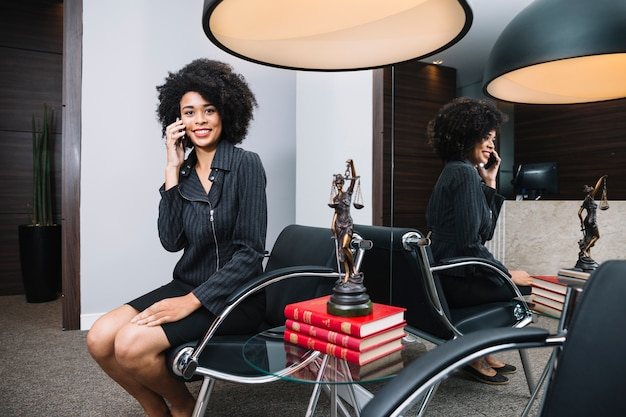Smiling african american woman talking on smartphone on armchair in office