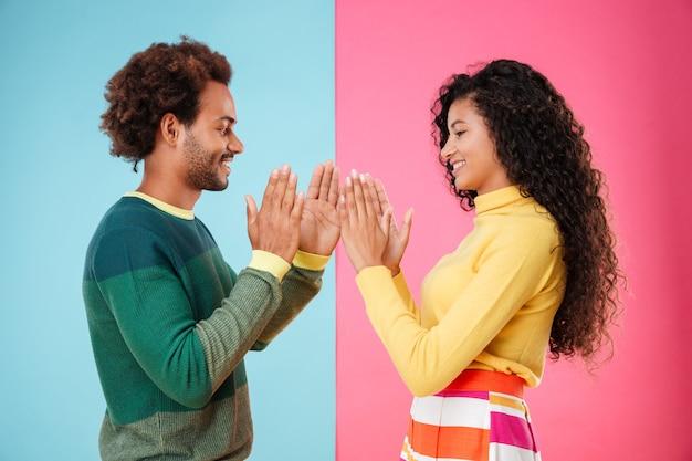 Улыбающаяся афро-американская молодая пара играет с пирожным