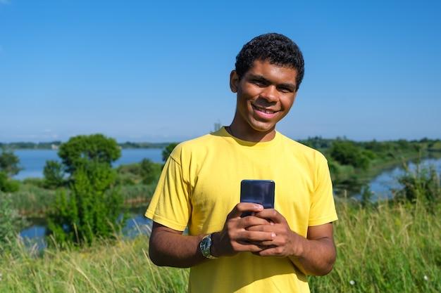 웃고 있는 아프리카계 미국인 청년은 야외에서 소셜 네트워크에서 의사소통을 합니다.