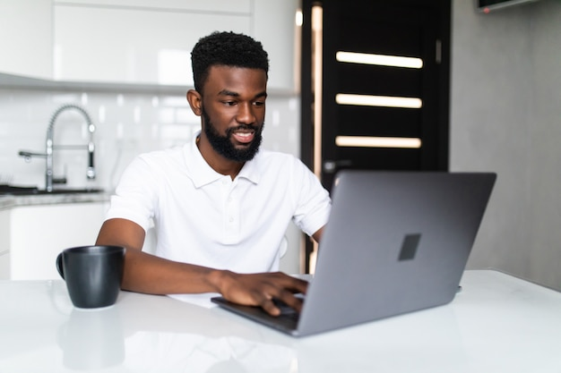 Smiling african american young man drinking coffee and using laptop on the kitchen