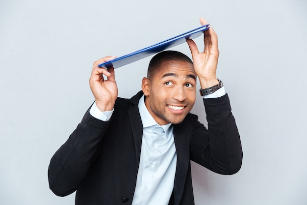 Smiling african american young man hiding under blue clipboard
