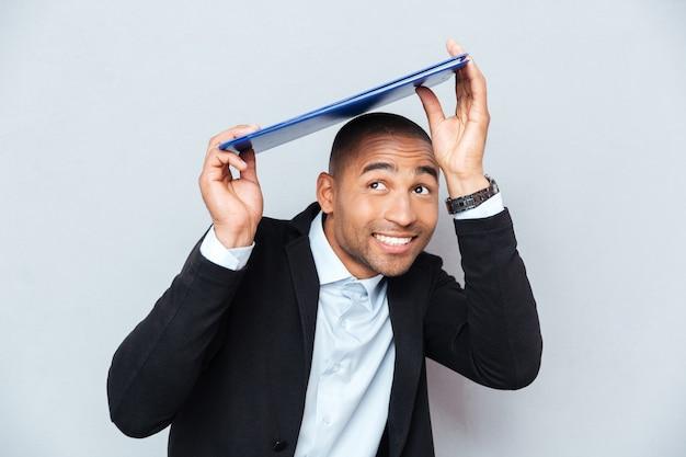 Улыбающийся афро-американский молодой человек прячется под синим буфером обмена