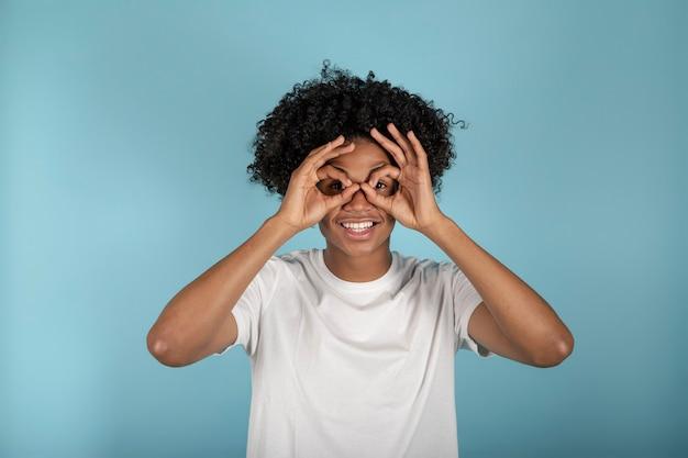 目の近くの手で基本的なカジュアルな白いtシャツ、パステルブルーの背景に分離されたメガネや双眼鏡、スタジオの肖像画を模倣して20代のアフリカ系アメリカ人の若い男を笑顔