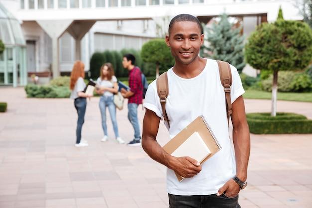 屋外に立っているバックパックと笑顔のアフリカ系アメリカ人の若い男の学生