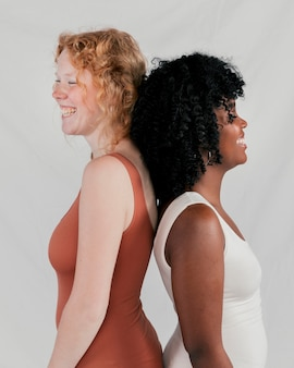 Smiling african and blonde young women standing back to back standing against grey backdrop