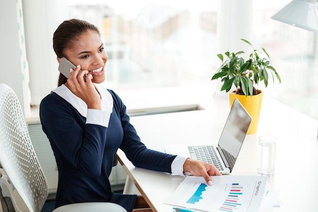 テーブルのそばに座って、オフィスで電話で話しているドレスを着て笑顔のアフリカのビジネス女性
