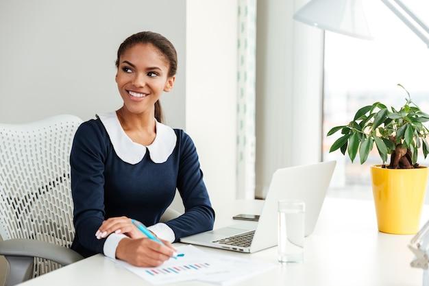 テーブルのそばに座って、職場のノートに何かを書くドレスを着て笑顔のアフリカのビジネス女性