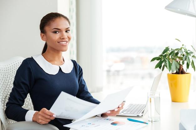 窓の近くに書類を持って職場に座って、オフィスでカメラを見てドレスを着て笑顔のアフリカのビジネス女性