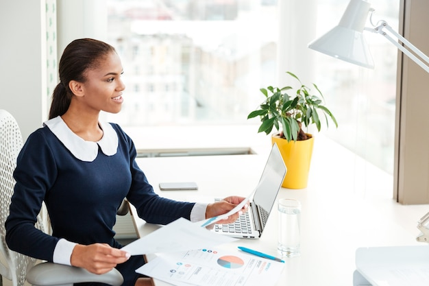 窓の近くに書類を持って職場に座って目をそらしているドレスを着て笑顔のアフリカのビジネス女性