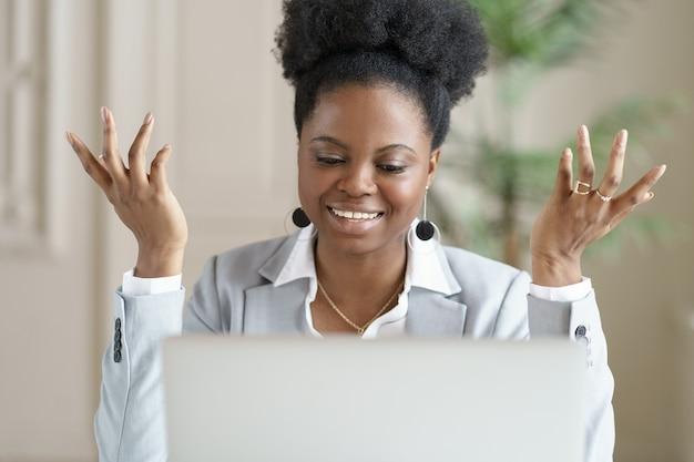 Улыбающаяся африканская бизнес-леди смотрит образовательный веб-семинар, разговаривает по видеочату или видеоконференции