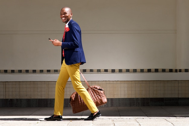Smiling african businessman walking with bag and phone