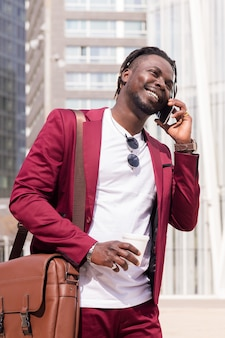 웃고 있는 아프리카 사업가가 전화로 이야기하며 걷는다