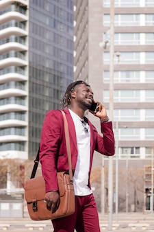 서류 가방을 들고 웃고 있는 아프리카 사업가가 전화 통화를 하며 도시를 걷습니다.