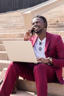 도시 계단에 앉아 컴퓨터 노트북과 전화로 일하는 웃고 있는 아프리카 사업가