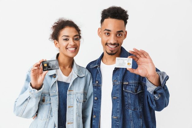 Smiling african couple in denim shirts holding credit cards  over grey wall