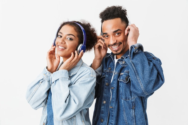 Smiling african couple in denim shirts listning music by headphones  over grey wall