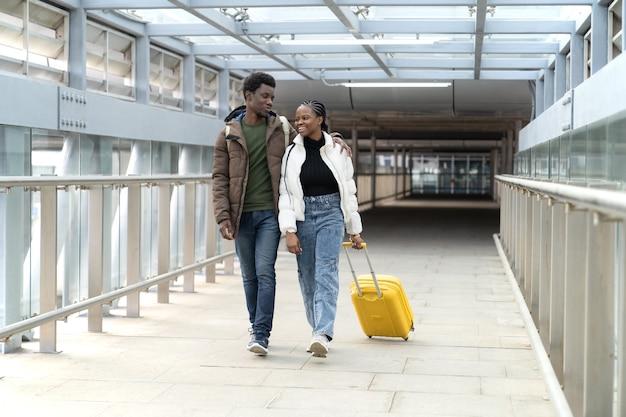 空港で笑顔のアフリカのカップルがスーツケース旅行で搭乗のために歩いて終了後のcovidロックダウン