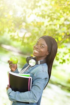 Smiling african female student holding an apple.