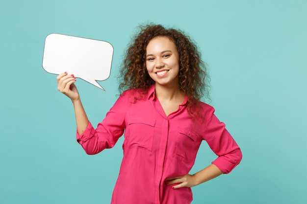 Smiling african girl in casual clothes holding empty blank say cloud, speech bubble isolated on blue turquoise wall background in studio. people sincere emotions lifestyle concept. mock up copy space.