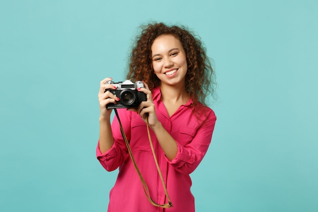Smiling african girl in casual clothes taking picture on retro vintage photo camera isolated on blue turquoise wall background in studio. people sincere emotions lifestyle concept. mock up copy space.