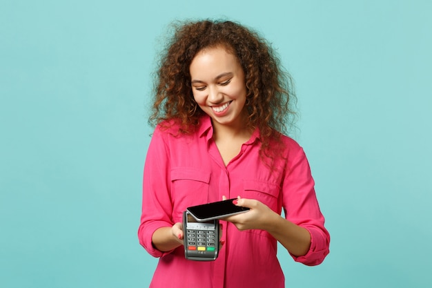 Smiling african girl hold mobile phone wireless modern bank payment terminal to process acquire credit card payment isolated on blue turquoise background. people lifestyle concept. mock up copy space.