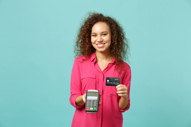Smiling african girl hold wireless modern bank payment terminal to process, acquire credit card payments isolated on blue turquoise background. people emotions, lifestyle concept. mock up copy space.