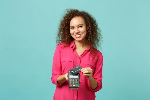 웃고 있는 아프리카 소녀는 무선 현대식 은행 결제 단말기를 들고 파란색 청록색 배경에서 분리된 신용 카드 결제를 처리합니다. 사람들의 감정, 라이프 스타일 개념. 복사 공간을 비웃습니다.