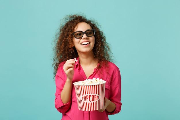 3d 아이맥스 안경을 쓴 웃고 있는 아프리카 소녀가 영화를 보고 스튜디오의 파란색 청록색 벽 배경에 격리된 팝콘을 들고 있습니다. 영화, 라이프 스타일 개념에서 사람들의 감정. 복사 공간을 비웃습니다.
