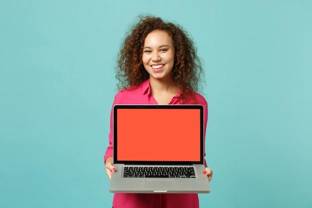 캐주얼한 옷을 입은 웃고 있는 아프리카 소녀는 스튜디오의 파란색 청록색 배경에 격리된 빈 화면이 있는 노트북 컴퓨터를 들고 있습니다. 사람들은 진심 어린 감정, 라이프 스타일 개념입니다. 복사 공간을 비웃습니다.