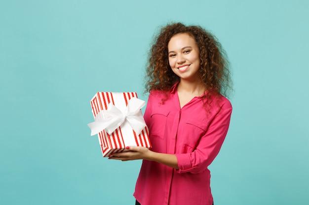 カジュアルな服装で笑顔のアフリカの女の子は、青いターコイズブルーの壁の背景に分離されたギフトリボンと赤い縞模様のプレゼントボックスを保持します。国際女性の日の誕生日の休日の概念。コピースペースをモックアップします。