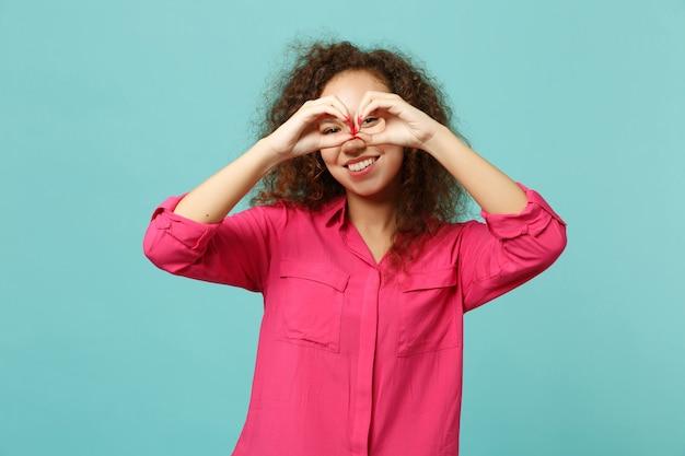 푸른 청록색 배경에 격리된 안경이나 쌍안경을 모방하여 눈 가까이에 손을 잡고 캐주얼 옷을 입고 웃고 있는 아프리카 소녀. 사람들은 진심 어린 감정, 라이프 스타일 개념입니다. 복사 공간을 비웃습니다.