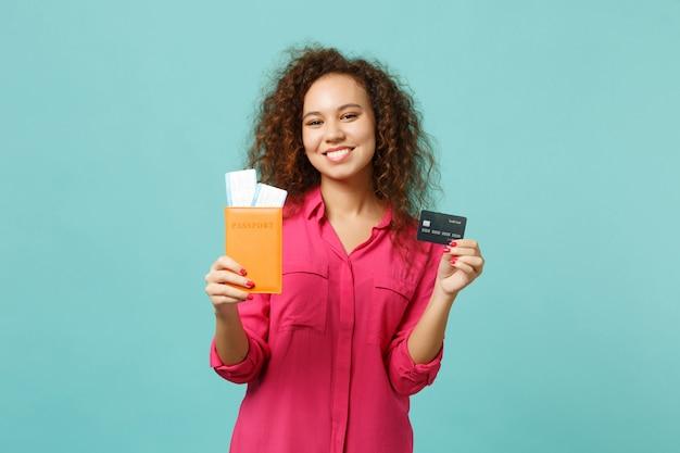 푸른 청록색 벽 배경에 격리된 여권 탑승권 신용 은행 카드를 들고 평상복을 입은 웃는 아프리카 소녀. 사람들은 진심 어린 감정 라이프 스타일 개념입니다. 복사 공간을 비웃습니다.