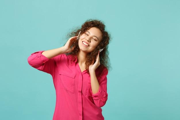 青いターコイズブルーの壁の背景に分離されたヘッドフォンで音楽を聴きながら、目を閉じてカジュアルな服を着て笑顔のアフリカの女の子。人々の誠実な感情、ライフスタイルのコンセプト。コピースペースをモックアップします。