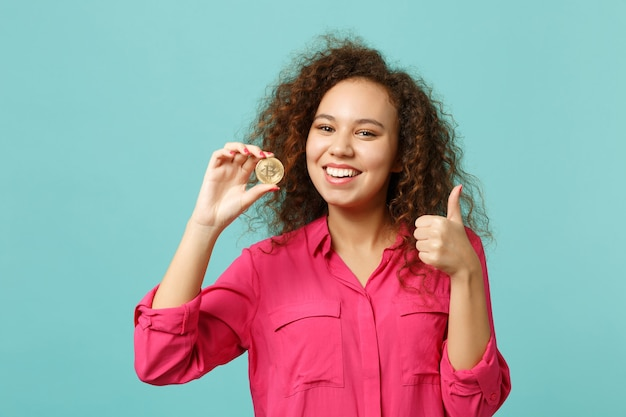 스튜디오에서 파란색 청록색 배경에 격리된 비트코인 미래 통화를 들고 엄지손가락을 치켜드는 캐주얼 옷을 입은 웃는 아프리카 소녀. 사람들은 진심 어린 감정 라이프 스타일 개념입니다. 복사 공간을 비웃습니다.