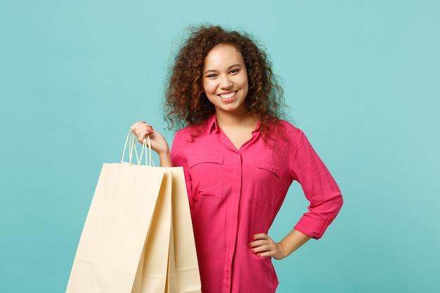 파란색 청록색 벽 배경에서 쇼핑을 한 후 구매한 패키지 가방을 들고 분홍색 캐주얼 옷을 입은 웃고 있는 아프리카 소녀. 사람들은 진심 어린 감정 라이프 스타일 개념입니다. 복사 공간을 비웃습니다.